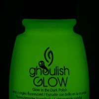 bottle of china glaze ghoulish glow in the dark nail polish glowing with the lights off